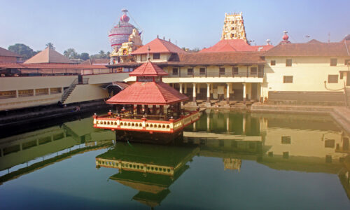 Holy Shrine dedicated to Hindu Deity, Lord Krishna. Picture taken in the town of Udupi, in the state of Karnataka, South India.   Picture shot on Feb 10, 2014, and shows the holy tank in the foreground, with the Temple towers seen in the background.  The building in the center of the tank, known as Mandapam, is where the sacred rituals are carried out. Four pillared corridors surround the tank with steps descending to the water.  This is for the convenience of devotees to take a dip in the holy tank, before entering the Temple. The holy tank here is named Madhava Sarovar, after the local saint Madhavacharya, who preached a form of Hinduism, several centuries ago.
